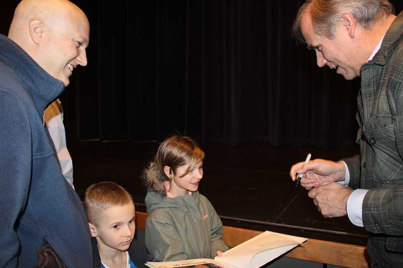 "HOLLY M. GILL/MADRAS PIONEER - U.S. Sen. Jeff Merkley, right, signs a memory book for the Russells, Lea, 8, Brooks, 6, and their father, Pastor Rick Russell, who traveled to Washington, D.C., last April. The Russells met with Merkley during his ""constituency hour,"" and memorialized the visit with photos. Russell said that his wife put the photo book together to help the children remember the visit, and Merkley wrote in book for the children."