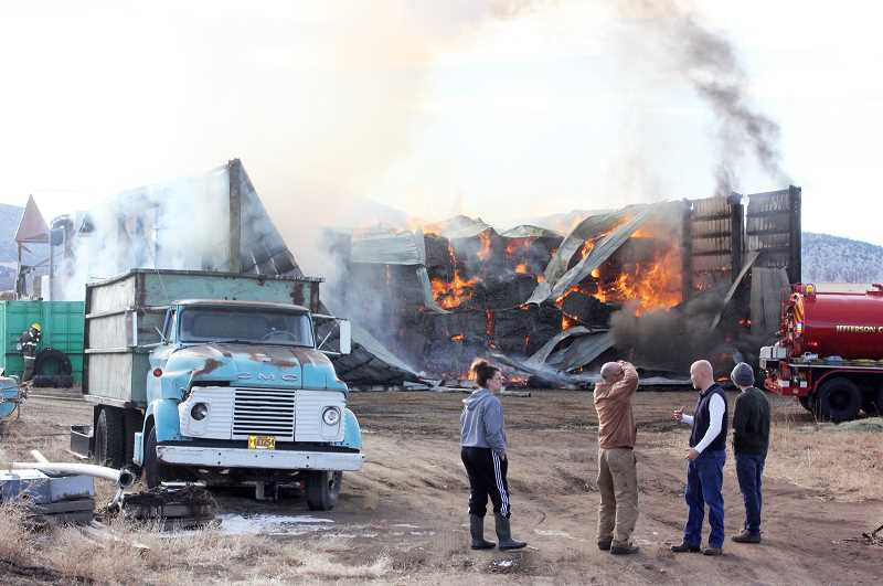 SUSAN MATHENY/MADRAS PIONEER - Bystanders watch as fire consumes a large hay shed filled with about 600 tons of alfalfa hay. The hay shed is located on Southwest Bear Drive, east of U.S. Highway 97, in the Culver area.