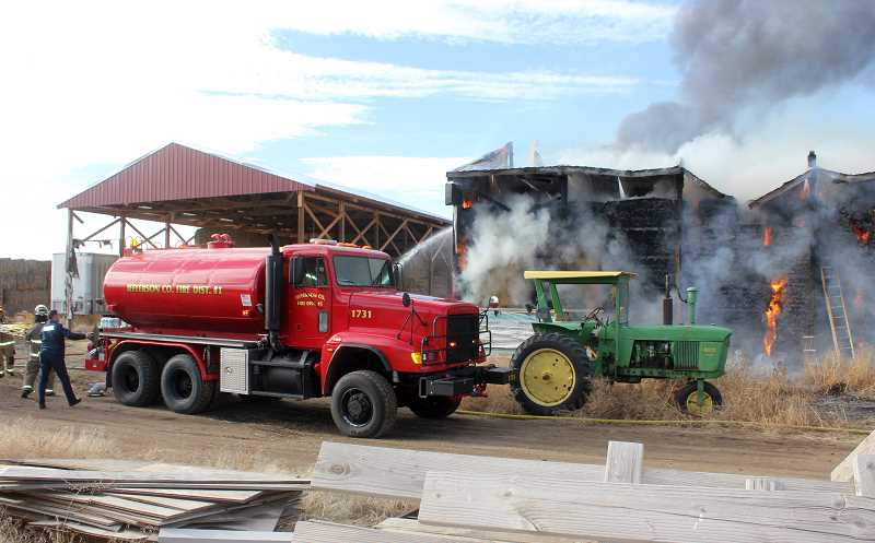 SUSAN MATHENY/MADRAS PIONEER - Firefighters hose down the hay to keep the fire from spreading to a second hay shed.