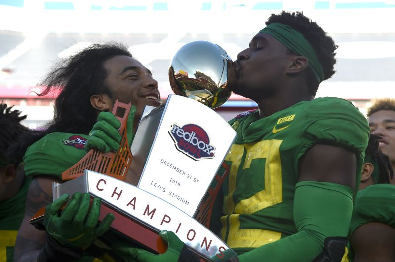 TRIBUNE PHOTO: GEROME WRIGHT - Outside linebacker La'Mar Winston (right) from Central Catholic High, who will return next season, and departing linebacker Kaulana Apelu enjoy a moment with the Redbox Bowl trophy after Oregon's 7-6 victory against the Michigan State Spartans.