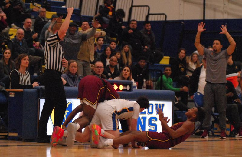 OUTLOOK PHOTO: DAVID BALL - The official makes a call on a tight play along the sideline where Barlows Jesse White collides with Central defender DeRay Seamster during the Rams 84-81 win Tuesday night.