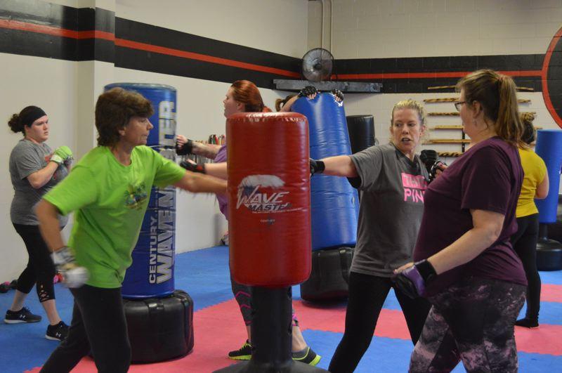 SPOTLIGHT PHOTO: NICOLE THILL-PACHECO - Instructor Susannah Garza, center, shows two women in her kickboxing fitness class the proper punching form. Garza is one of two instructors who leads kickboxing fitness classes designed for women in St. Helens.