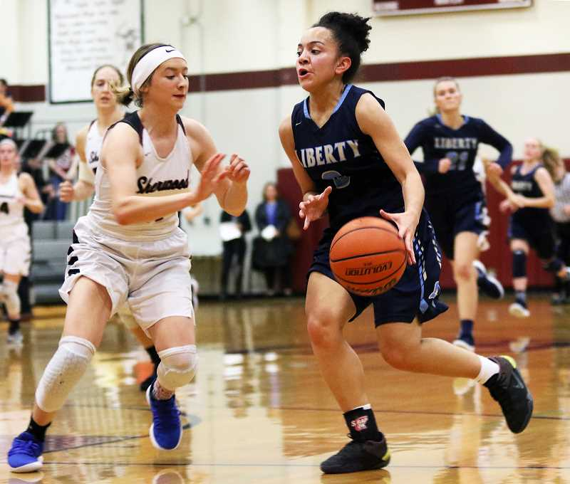 PMG FILE PHOTO: DAN BROOD - Liberty sophomore Taylin Smith (right) looks to drive past Sherwood junior Ava Boughey during the Falcons' game against Sherwood, Wednesday, Jan. 9, at Sherwood High School.