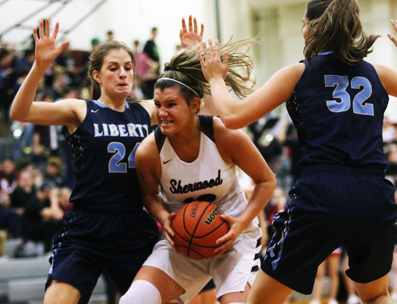 TIMES PHOTO: DAN BROOD - Sherwood senior post Kaytlin Cooke (center) looks to go up to the basket betwen Liberty's Clara Robbins (left) and Alyssa Chronister during the Lady Bowmen's 43-33 win.