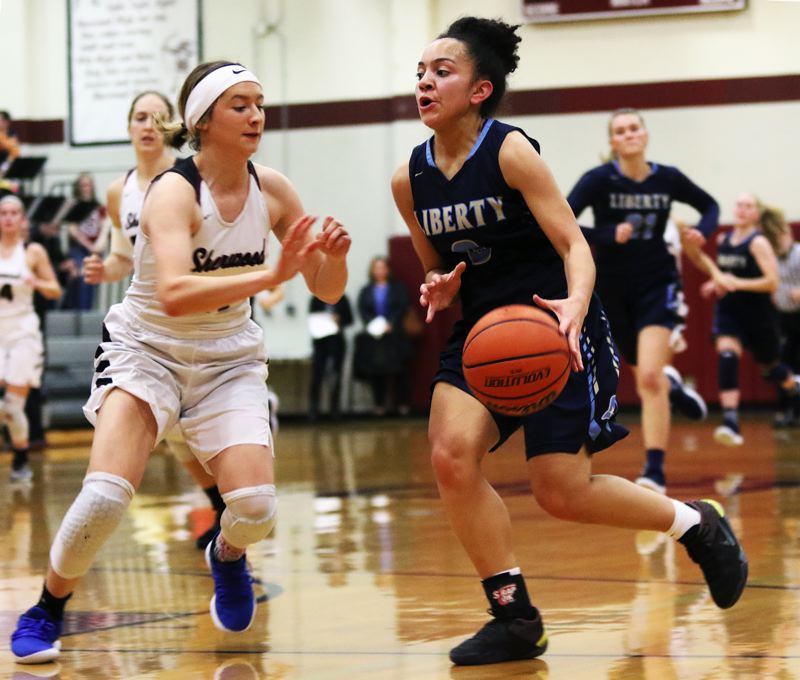 TIMES PHOTO: DAN BROOD - Liberty sophomore guard Taylin Smith (right) looks to get past Sherwood junior Ava Boughey.
