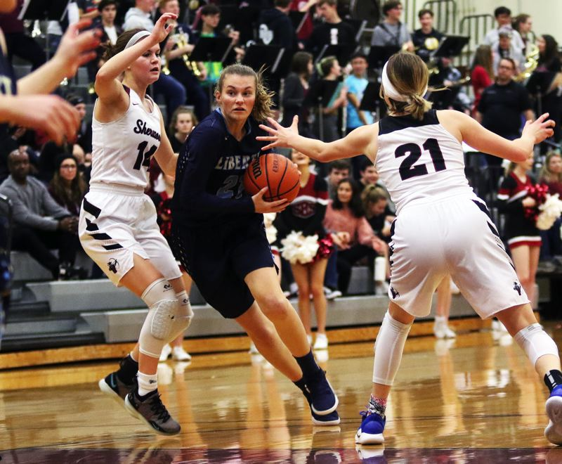 TIMES PHOTO: DAN BROOD - Liberty junior Alexa Smith looks to drive between Sherwood's Alex Verkamp (left) and Ava Boughey.