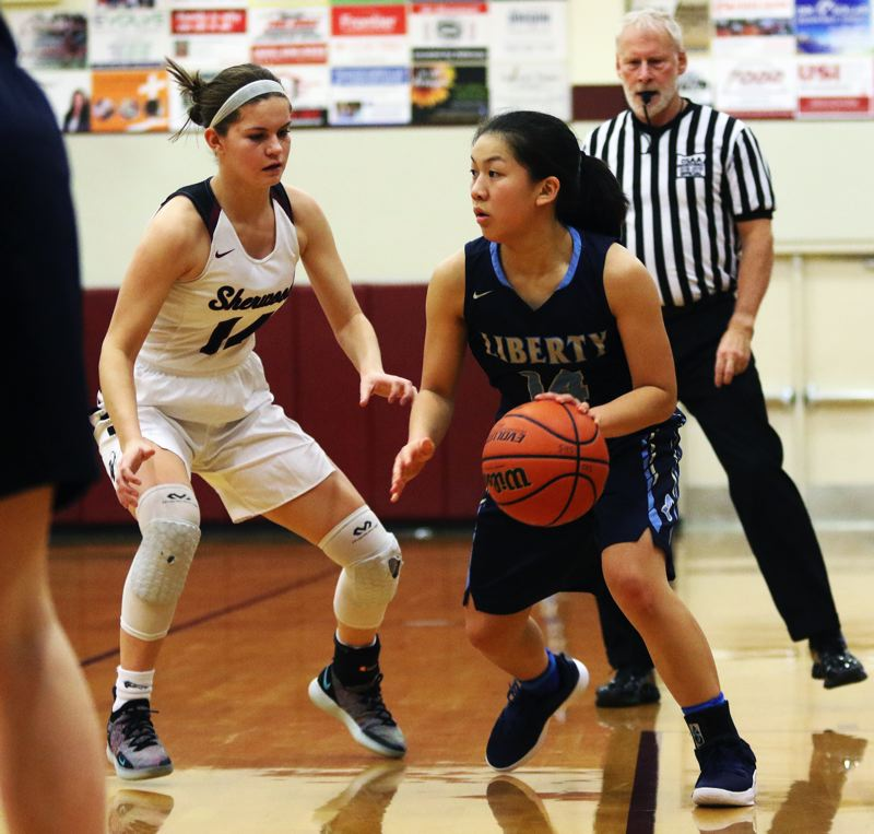 TIMES PHOTO: DAN BROOD - Liberty senior Emily Le (left) looks to get past Sherwood senior Alex Verkamp during the Pacific Conference opener.