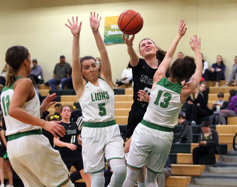 TIDINGS PHOTO: MILES VANCE - Tigard senior guard Campbell Gray splits two West Linn defenders to score during her team's 63-46 win at West Linn High School on Friday.