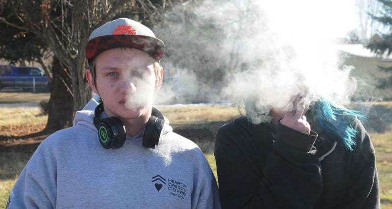 FILE PHOTO - Two teenagers can be seen smoking tobacco in a park in this file photo .