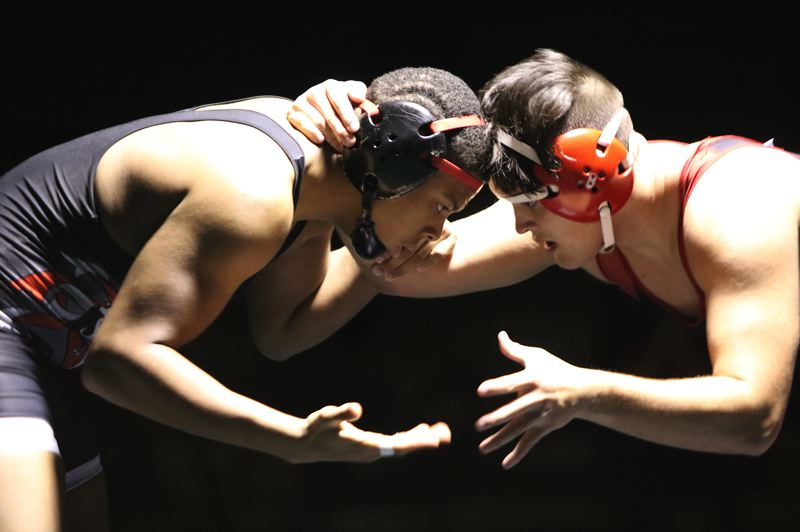 PAMPLIN MEDIA: JIM BESEDA - David Douglas junior Josiah Green, left, squared off with Clackamas' Domonic Chimienti at 195 pounds, winning a 5-3 decision that clinched the Scots' dual win last Thursday.