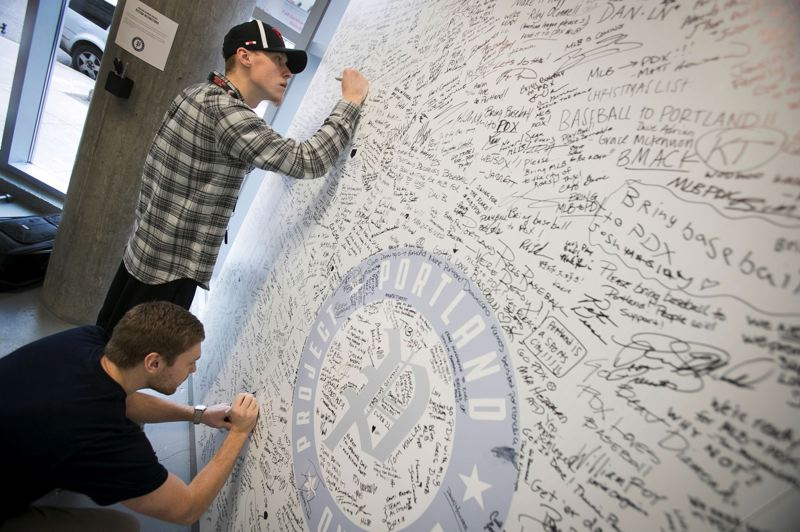 TRIBUNE PHOTO: JAIME VALDEZ - Canon Cravens (lower left), 23, Corvallis, and his brother, Cyrus, 26, sign their support for a Major League Baseball team to Portland at the MLB-to-PDX pop-up shop.