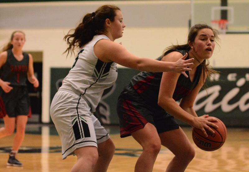 SANDY POST: DAVID BALL - Sandys Tana Dwyre protects the ball from Reynolds defender Christina Chernoff during the Pioneers 47-28 road win Friday.