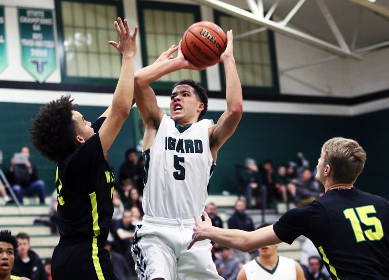 TIMES PHOTO: DAN BROOD - Tigard sophomore Drew Carter (5) looks to shoot over West Linn junior Bryson Crockett during Friday's Three Rivers League game. The Tigers got a 66-63 victory.