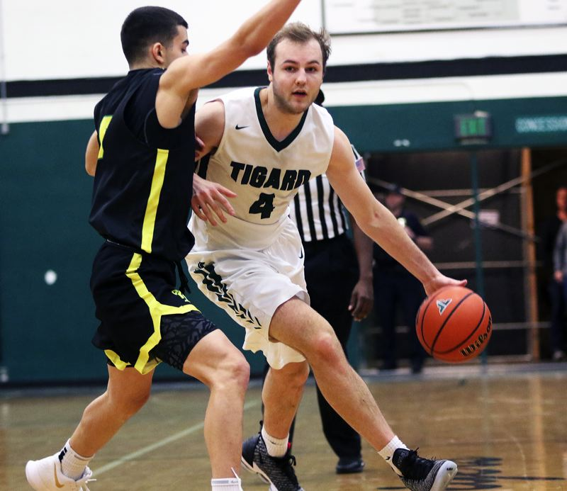 TIMES PHOTO: DAN BROOD - Tigard senior Stevie Schlabach (right) tries to drive past West Linn junior Chris Zakariya during Friday's game. Schlabach scored 25 points in the Tigers' 66-63 victory.