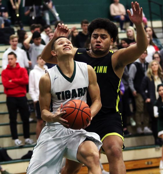 TIMES PHOTO: DAN BROOD - Tigard senior Jazz Ross (left) looks to go up to the basket against West Linn junior Damiko Tidmore Jr. during the second half of Friday's game.