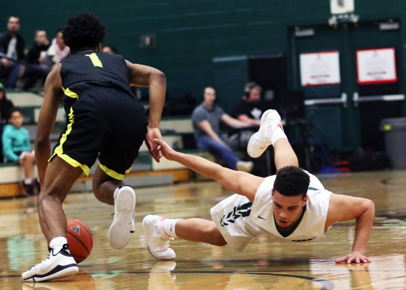 TIMES PHOTO: DAN BROOD - West Linn junior Micah Garrett (left) heads toward the basket after Tigard junior Max Lenzy dove for a loose ball during Friday's game.