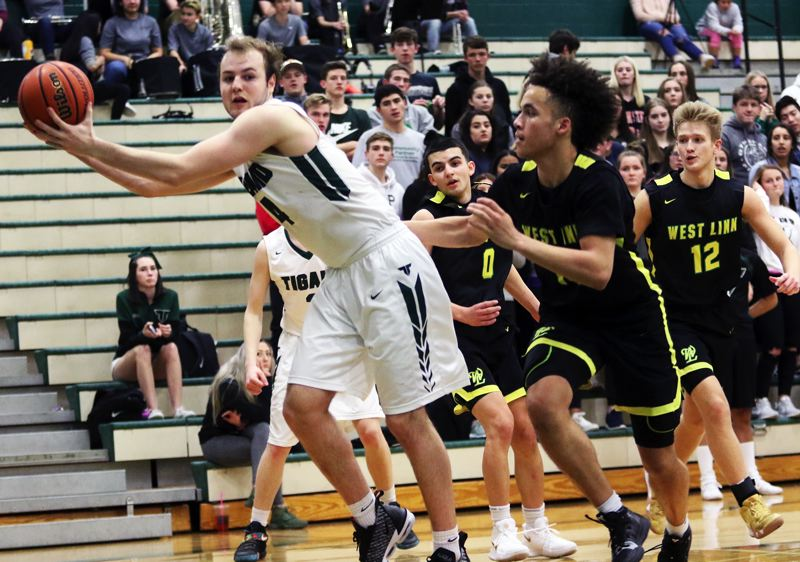 TIMES PHOTO: DAN BROOD - Tigard senior Stevie Schlabach (left) grabs the ball just before it goes out of bounds over the baseline during Friday's game.