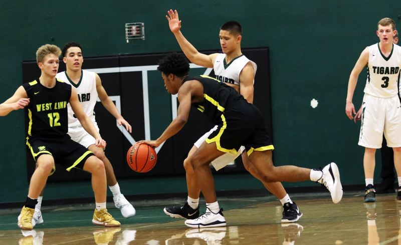 TIMES PHOTO: DAN BROOD - Tigard senoir Jazz Ross plays tight defense against West Linn junior Micah Garrett during Friday's Three Rivers League contest.