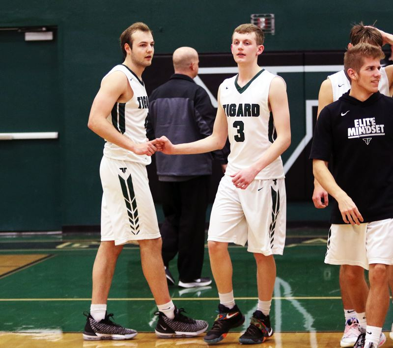 TIMES PHOTO: DAN BROOD - Tigard seniors Stevie Schlabach (left) and Jake Bullard congratulate each other following the Tiger' 66-63 win over West Linn on Friday.