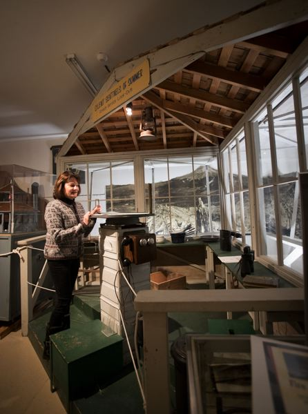 PAMPLIN MEDIA GROUP: JAIME VALDEZ - Diane Lokting, development director for the Mt. Hood Cultural Center and Museum, stands by a Forest Service look-out display in the Forest Gallery portion of the museum. The display features authentic memorabilia, including a firefinder, a piece of equipement that was used to determine the location of forest firest.