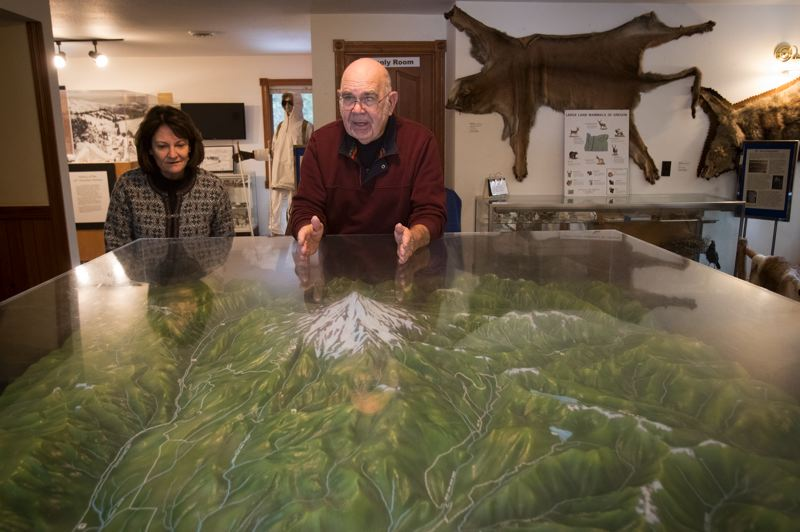 PAMPLIN MEDIA GROUP: JAIME VALDEZ - Diane Lokting, left, development director of the Mt. Hood Cultural Center and Museum, and curator Lloyd Musser explain how a topographical map of the Mount Hood area made its way from the garage of a donor to the museum.