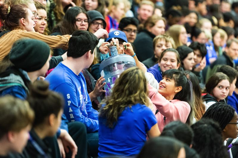 STAFF PHOTO: CHRISTOPHER OERTELL - To kick off the fundraising efforts, students and staff put money into a jug and passed it around during Friday's assembly.