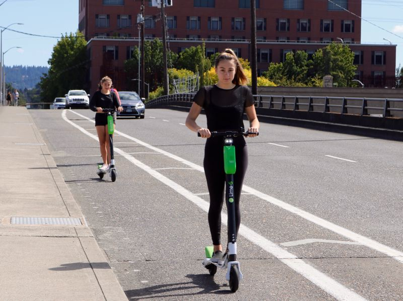TRIBUNE PHOTO: ZANE SPARLING - Two e-scooters riders zip along in Portland in 2018.