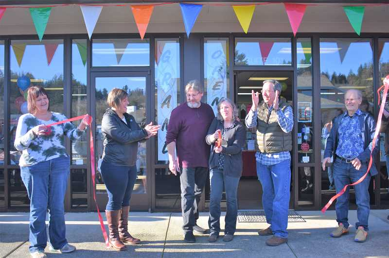 ESTACADA NEWS PHOTO: EMILY LINDSTRAND - Community members cheer after Dave and Ellen Anderson complete the ribbon cutting during the grand opening celebration for The Artsmith last weekend.