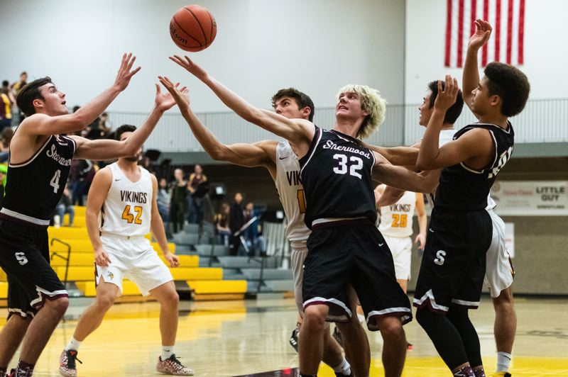 PMG PHOTO: CHRISTOPHER OERTELL - Sherwood High School junior Blake Jensen (32) and senior Ryan Sandilands reach for the ball during the Bowmens win at Forest Grove on Friday.