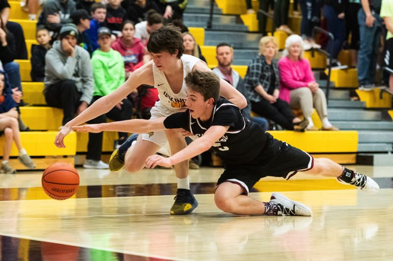 PMG PHOTO: CHRISTOPHER OERTELL - Sherwood High School sophomore Asher Krauel (5) dives for the ball during the Bowmens 59-55 victory at Forest Grove.