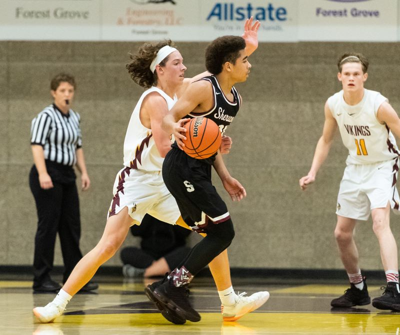 PMG PHOTO: CHRISTOPHER OERTELL - Sherwood junior guard Jamison Guerra looks to make a move with the ball during the Bowmens victory at Forest Grove.