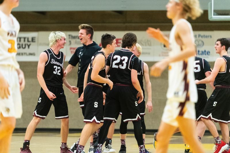 PMG PHOTO: CHRISTOPHER OERTELL - Members of the Sherwood High School boys basketball team celebrate following the Bowmens 59-55 win at Forest Grove.