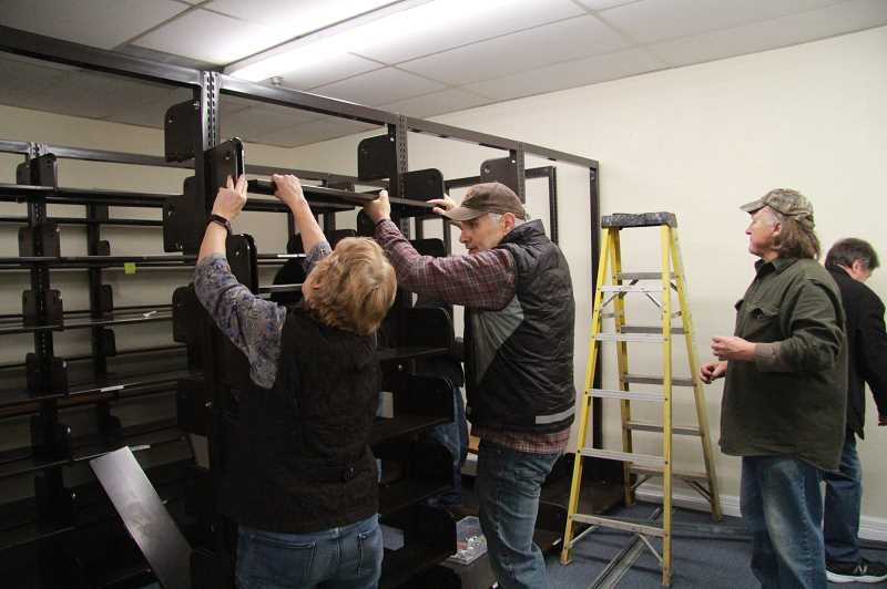 REVIEW PHOTO: SAM STITES - Husband-and-wife duo and Friends volunteers Barbara Auburn and Kevin House (left and center) install shelving at Booktique's new location as Dan Ogren (right) supervises construction.