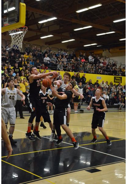 PHOTO COURTESY: JOHN BREWINGTON - St. Helens and Scappoose High players battle for the ball under the basket during their league game at St. Helens.