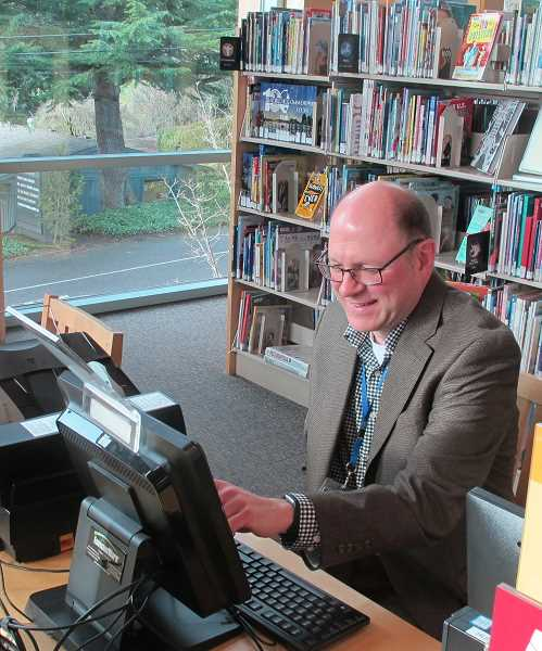 Hillsdale Library Branch Manager Jay Hadley.  Trees on Sunset Boulevard can be seen through the windows.