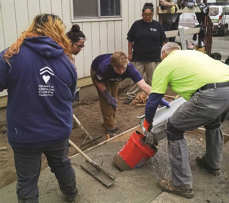PHOTO SUBMITTED BY COLIN PRICE - Members of Heart of Oregon's local YouthBuild program pour concrete for the new Prineville facility.