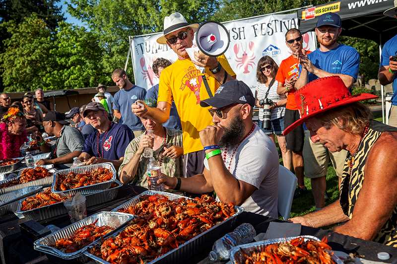 FILE PHOTO: JON HOUSE - Mayor Lou Ogden, sporting a fedora and megaphone, serves as timekeeper for the crawfish-eating contest in 2017.