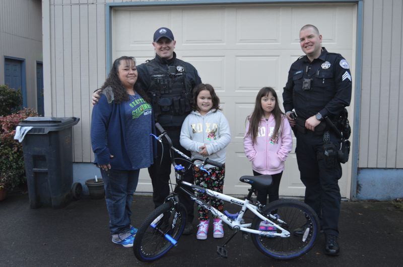 SPOTLIGHT PHOTO: NICOLE THILL-PACHECO - Linda Banuelos, St. Helens Police Department Officer Bryan Cutright, Aiyanna Simpkins, Roxanne Simpkins and Evin Eustice pose for a group photo with the bicycle that was donated to Sebastian Simpkins in December. Banuelos said the gift has been great for the entire family, including her daughters, who were excited for their brother to receive the gift.