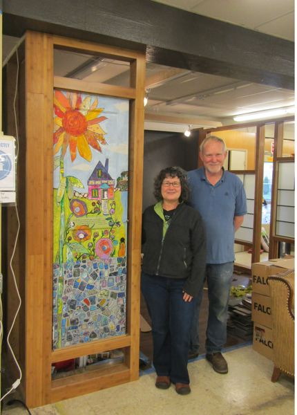 PHOTO COURTESY OF JENNIFER ANDERSON - Artist Luanne Kreutzer and ReStore manager Dave Marble pose near a glass collage Kreutzer created that will be incorporated into a doorway for the ReStores Showcase Gallery. Funding for the gallery creation was made possible through a grant from the Columbia County Cultural Coalition.