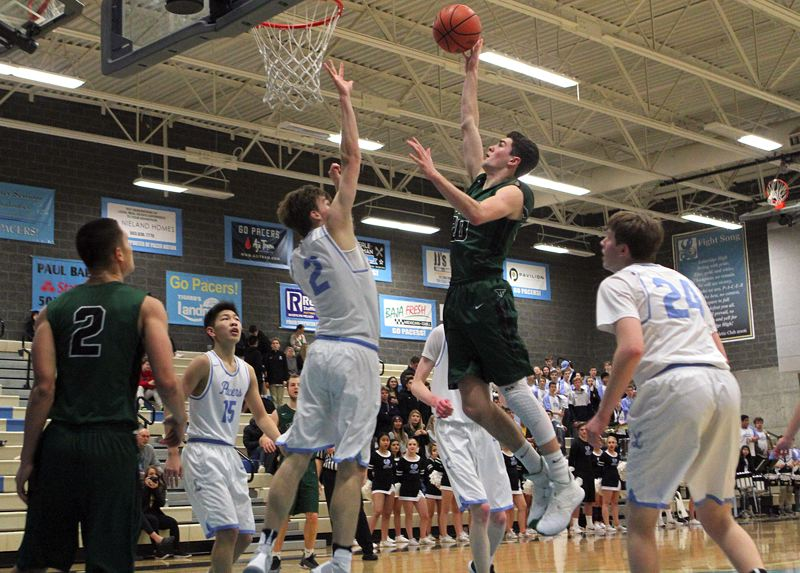 REVIEW PHOTO: MILES VANCE - Tigard's Luke Ness lofts a shot over Lakeridge's Calvin Migchelbrink during the Tigers' 69-59 win at Lakeridge High School on Friday night.