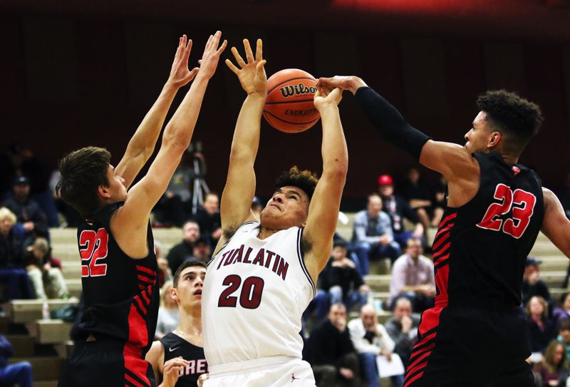 TIMES PHOTO: DAN BROOD - Tualatin junior John Miller (20) tries to go up to the basket against Oregon City junior Jake Gettel (left) and Erich Nova during Friday's game.