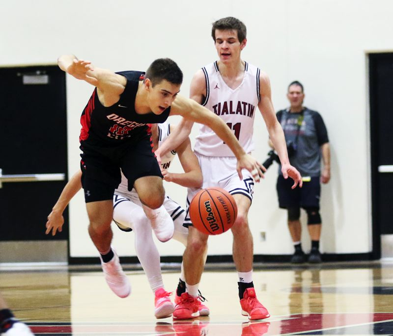 TIMES PHOTO: DAN BROOD - Oregon City senior Corban Remsburg (left) goes after a loose ball during the Pioneers' 61-60 win at Tualatin on Friday.