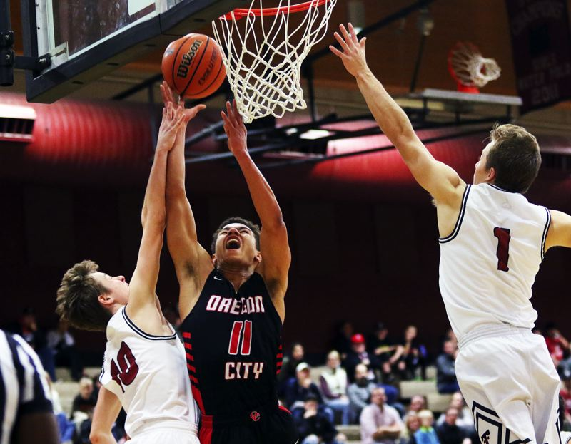 TIMES PHOTO: DAN BROOD - Oregon City junior Andre Best (11) goes up to the basket against Tualatin senior Derek Leneve during Friday's game.