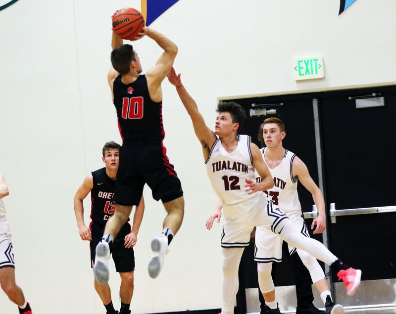 TIMES PHOTO: DAN BROOD - Oregon City senior Corban Remsburg (10) goes up high to shoot over Tualatin junior Sam Noland during Friday's game.