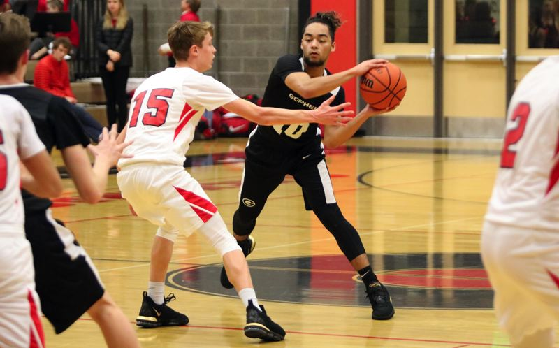 PAMPLIN MEDIA: JIM BESEDA - Gresham's Daello Portin-Chapman (10) looks to make a pass under pressure from Clackamas' Jack Dorn (15) during the Gophers' 61-60 Mt. Hood Conference road win Friday at Clackmas.