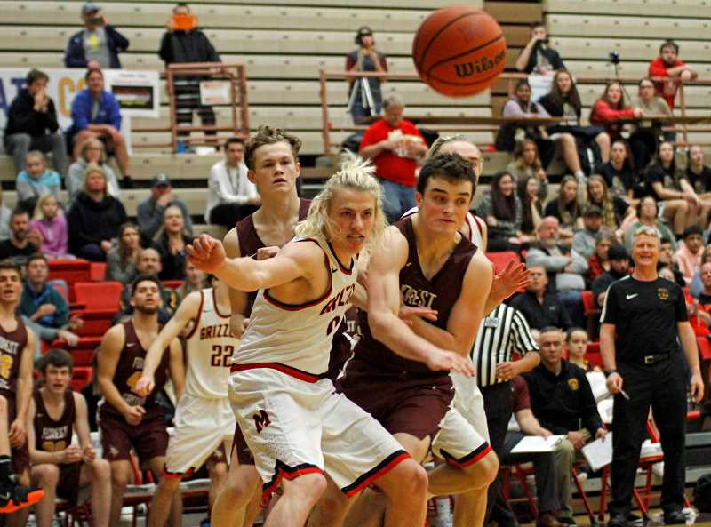 STAFF PHOTO: WADE EVANSON - Forest Grove's Ayden Purcell battles for a rebound with McMinnville's Luke Arzner during the Vikings' game against the Grizzlies Saturday, June 19, at Linfield College in McMinnville.