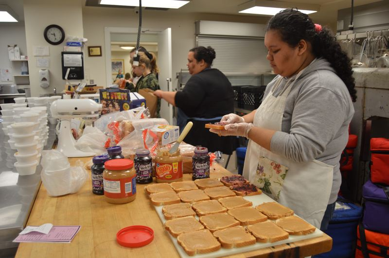 SPOTLIGHT PHOTO: NICOLE THILL-PACHECO - St. Helens High School freshman Jacqueline Meabe, right, volunteers on Monday, Jan. 21, by preparing sandwiches for food bags to be handed out by Community Action Team. In the background, Jacquelines mom, Jennifer Meabe, and seventh-graders Ayla Clark and Bridget Kishpaugh add chips and other items to the food bags.