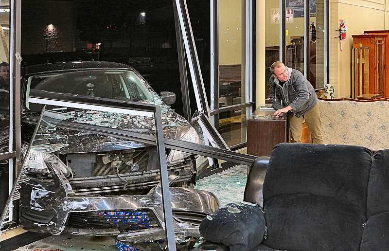 DAVID F. ASHTON - Inside the thrift store, a worker began to clean up after a car smashed through the business front plate-glass windows.