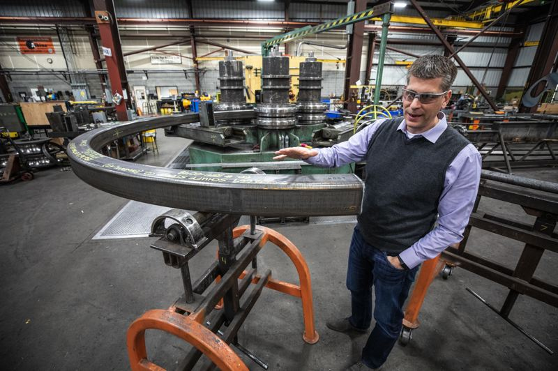 TRIBUNE PHOTO: JONATHAN HOUSE - Albina Co. President Brian Smith discusses the process of bending steel.