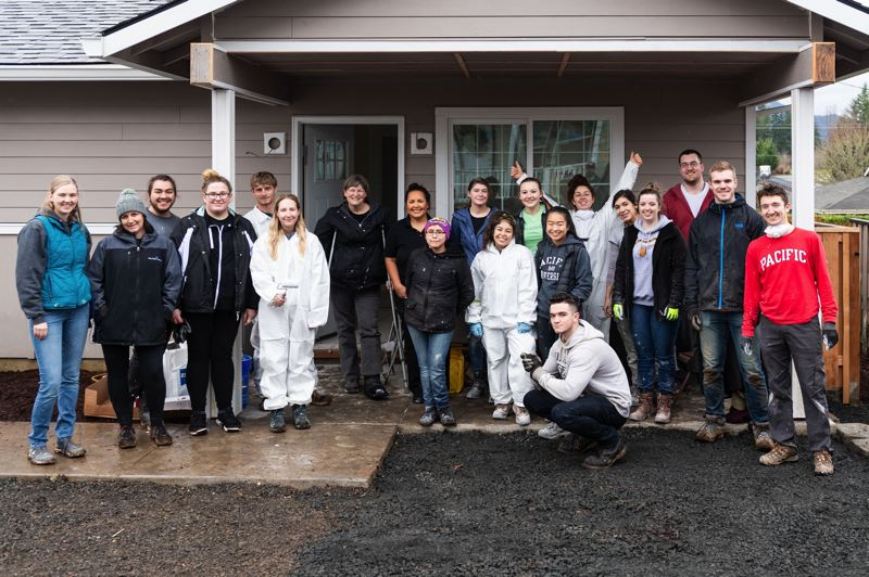 STAFF PHOTO: CHRISTOPHER OERTELL - Pacific University students pose for a photo alongside West Tuality Habitat for Humanity volunteer services coordinator Emma Morton, far left, outside of a single-story home being built at Kidd Court in Forest Grove on Thursday, Jan. 17.